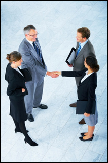 Four business dressed people shaking hands.